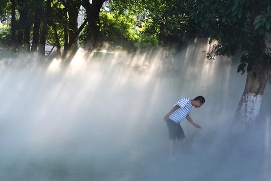 """重庆公园推广喷雾降温 市民雾里出行入""""仙境"""""""