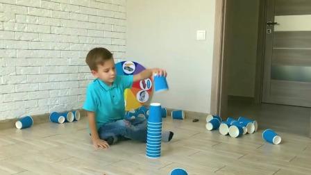 小男孩骑着着自己的玩具汽车玩纸杯游戏!
